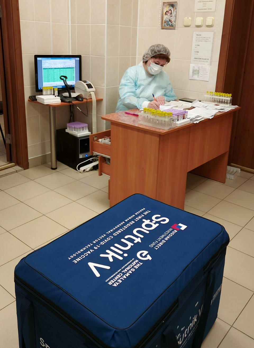 In this handout photo released by Belarus Health Ministry, Belarus medical worker works with the documentation of the Russia's Sputnik V coronavirus vaccine in Minsk, Belarus, Tuesday, Dec. 29, 2020. Belarus has announced the start of mass coronavirus vaccinations with the Russian-developed Sputnik V shot, becoming the second country after Russia to roll out the vaccine that is still undergoing late-stage studies to ensure its safety and efficacy. (Julia Borodun/ Belarus Health Ministry via AP)