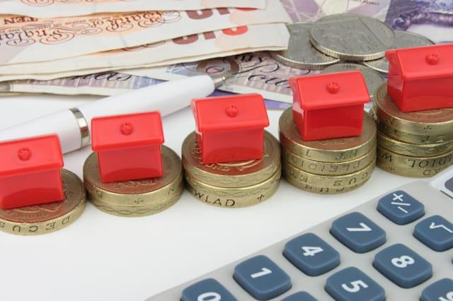 a red houses sitting on a coins ...