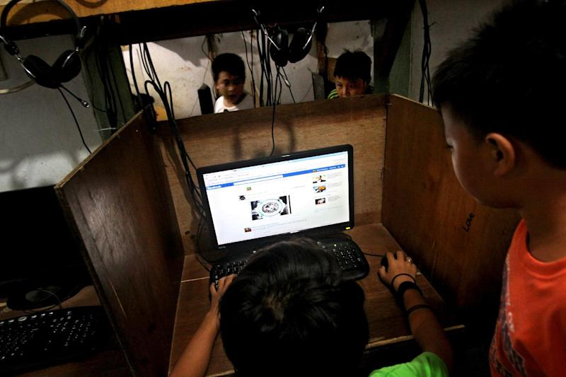 In this June 19, 2013 photo, an Indonesian youth browse his Facebook page at an internet cafe in Jakarta, Indonesia. The use of social networking to groom potential attackers is posing a new challenge to authorities in the world's most populous Muslim country that has been struggling to eradicate militant groups. (AP Photo/Tatan Syuflana)