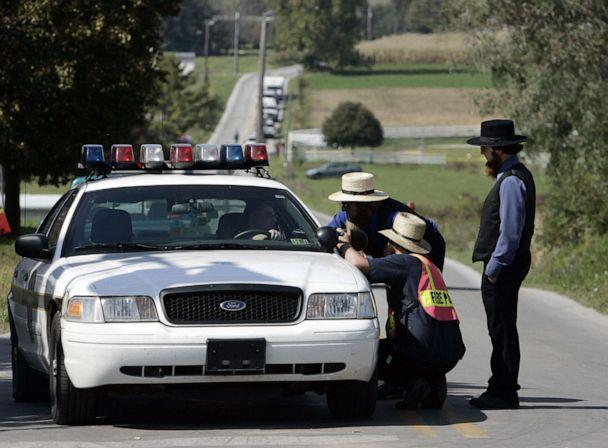 PHOTO: Amish men speak with a police officer on a road leading to the one-room West Nickel Mines Amish School, Oct. 3, 2006, in the town of Nickel Mines, Penn. a day after a shooting at the school left three girls dead. (Stan Honda/AFP/Getty Images)