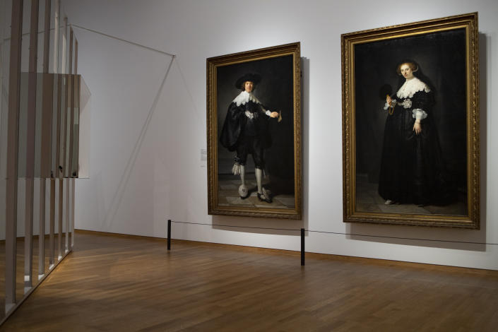 Oopjen Coppit, right, in a full-length portrait painted in 1664 by Rembrandt van Rijn, is seen at the Slavery exhibition at The Rijksmuseum in Amsterdam, Monday May 17, 2021. Coppit, was the widow of a man whose father owned Amsterdam's largest sugar refinery, processing crops harvested by enslaved men and women in South America. She is the personification of the wealth generated for a privileged few by the vast numbers of enslaved workers, and part of a pair of paintings that also included a depiction of her first husband Marten, left. (AP Photo/Peter Dejong)