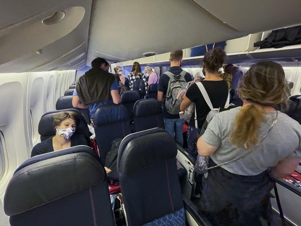 Passengers board an Air France flight bound for Paris at Johannesburg's OR Tambo airport Monday Dec. 21 2020. More and more countries around the world are restricting travel from Britain and elsewhere, including South Africa, amid concerns about new strains of the coronavirus. (AP Photo/Jerome Delay)