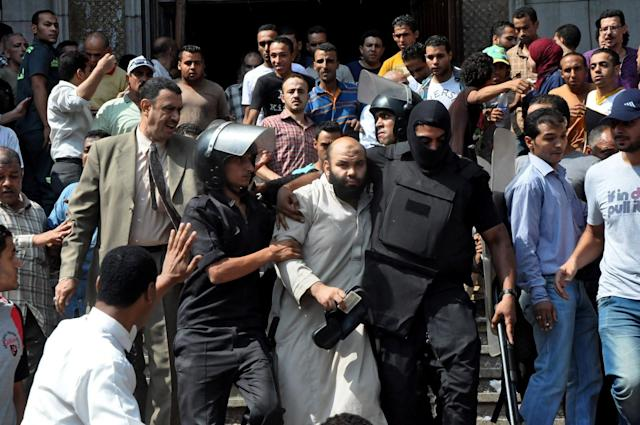 Egyptians security forces escort an Islamist supporter of the Muslim Brotherhood out of the al-Fatah mosque, after hundreds of Islamist protesters barricaded themselves inside the mosque overnight, following a day of fierce street battles that left scores of people dead, near Ramses Square in downtown Cairo, Egypt, Saturday, Aug. 17, 2013. Authorities say police in Cairo are negotiating with people barricaded in a mosque and promising them safe passage if they leave. Muslim Brotherhood supporters of Egypt's ousted Islamist president are vowing to defy a state of emergency with new protests today, adding to the tension. (AP Photo/Hussein Tallal)