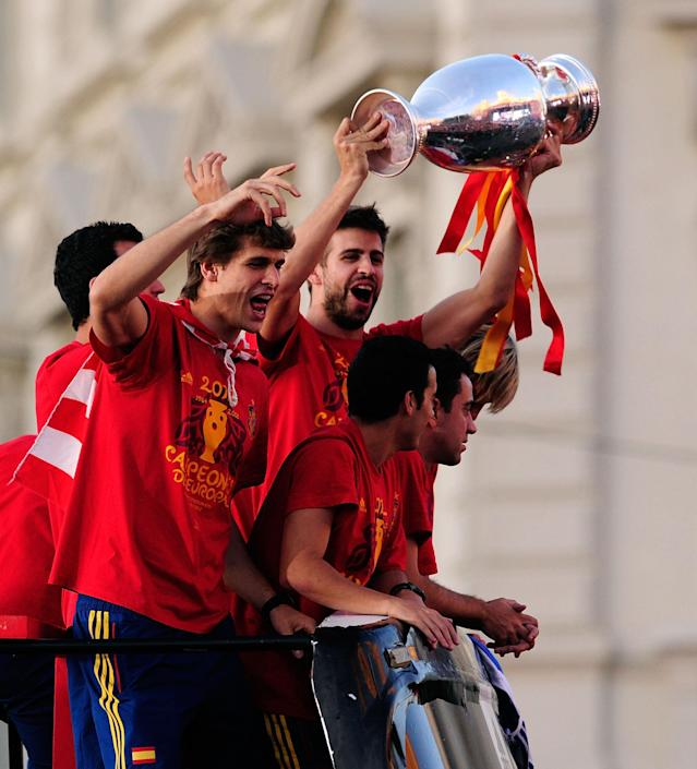 MADRID, SPAIN - JULY 02: Gerard Pique holds the UEFA EURO 2012 trophy aloft beside team-mate Fernando Llorente while celebrating with fellow players as they parade the UEFA EURO 2012 trophy on a double-decker bus on July 2, 2012 in Madrid, Spain. Spain beat Italy 4-0 in the UEFA EURO 2012 final match in Kiev, Ukraine, on July 1, 2012. (Photo by Denis Doyle/Getty Images)