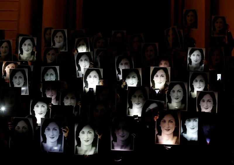 FILE PHOTO: People hold up photos of anti-corruption journalist Daphne Caruana Galizia during a protest marking eighteen months since her assassination, outside the office of Prime Minister Muscat in Valletta
