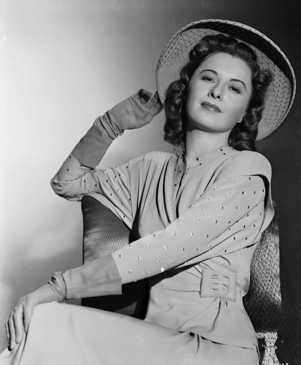 <p>Barbara Stanwyck wears a wrap dress with dolman sleeves, accessorized with a hat and gloves. </p>