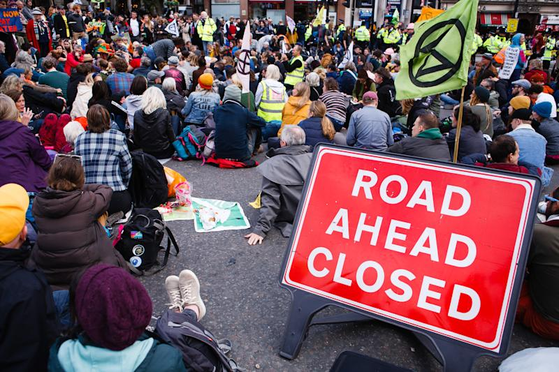 Members of climate change activist movement Extinction Rebellion (XR) sit in the road at Trafalgar Square on the fourth day of the group's two-week 'International Rebellion' in London, England, on October 10, 2019. By lunchtime Thursday police had all but contained the demonstrations in Trafalgar Square and the roadways around it, where sizeable numbers of XR followers remained. A hearse carrying a coffin for 'Our Future', which had been parked at the Whitehall exit from the square since Monday, was removed early afternoon. (Photo by David Cliff/NurPhoto via Getty Images)