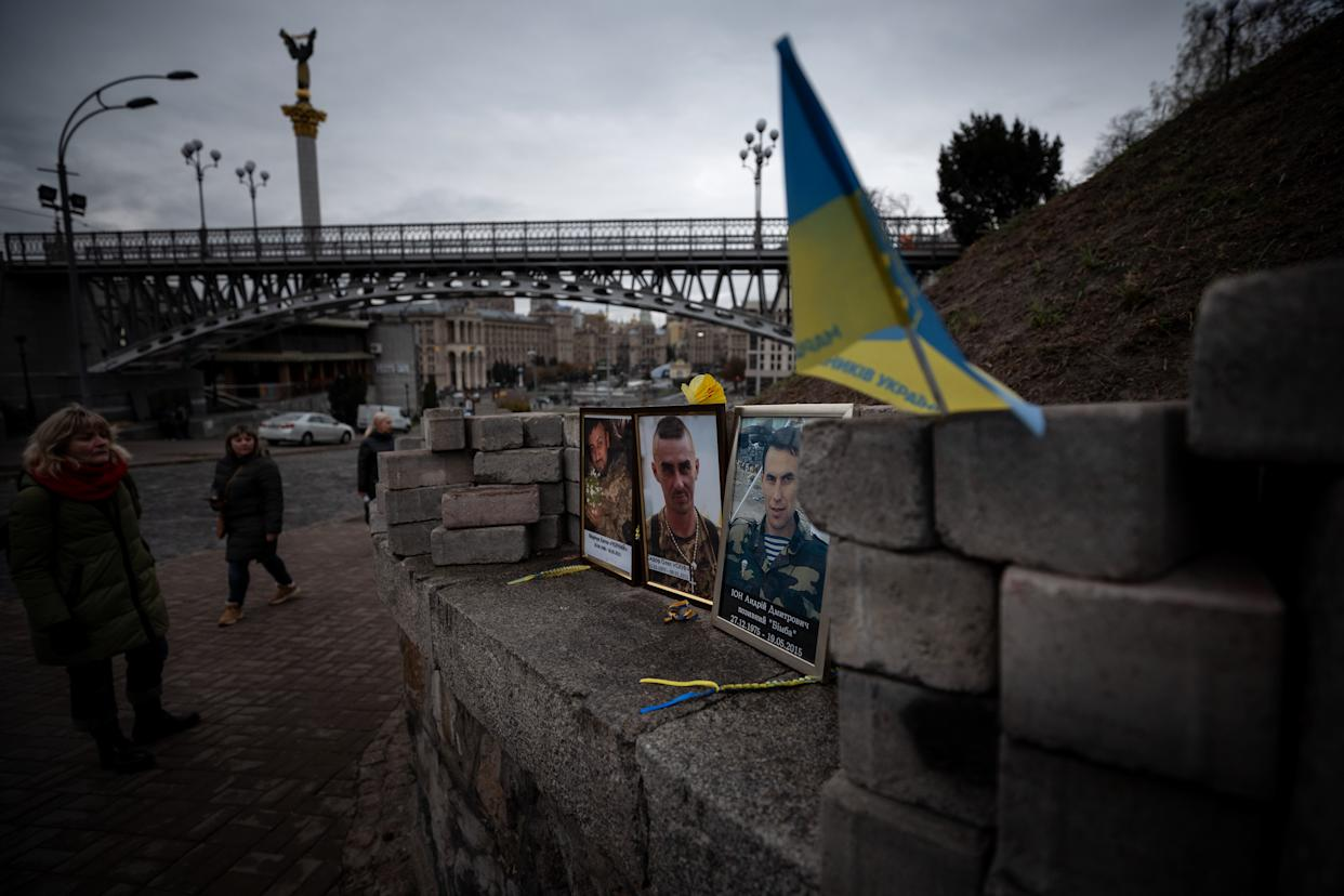 """A women looks at the photos of protesters who were killed during the Euromaidan revolution at the memorial of """"Heavenly 100"""" at Independence square in Kiev, Ukraine on October 28, 2019. (Photo: Agron Dragaj for Yahoo News)"""