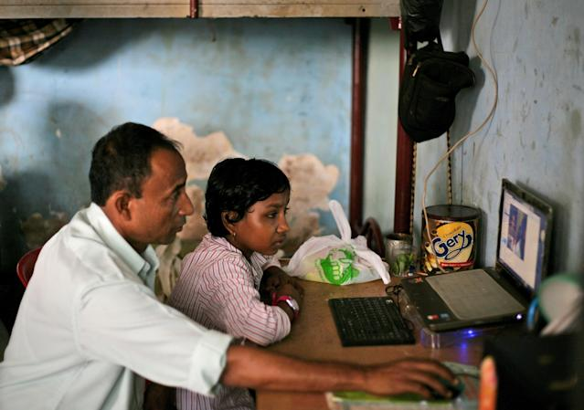 "In this Oct. 20, 2013 photo, young ethnic Rohingya asylum seeker Senwara Begum, right, is helped by her foster father, Shamsul bin Sayed, to use Skype to talk to her family members in Myanmar from their temporary shelter in Medan, North Sumatra, Indonesia. ""I'm fine,"" Senwara says, trying to sound upbeat. ""I'm with a family that is taking good care of me. They love me. I'm learning things, English and religion."" Her father reminds her to be a good girl. He is desperate to see his children again, but believes they are better off far away. (AP Photo/Binsar Bakkara)"