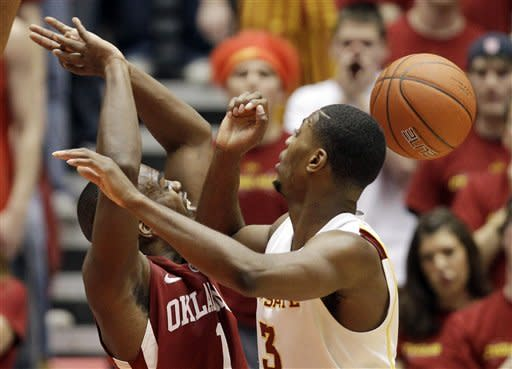 Oklahoma guard Sam Grooms, left, loses the ball while driving to the basket in front of Iowa State forward Melvin Ejim, right, during the first half of an NCAA college basketball game, Saturday, Feb. 18, 2012, in Ames, Iowa. (AP Photo/Charlie Neibergall)