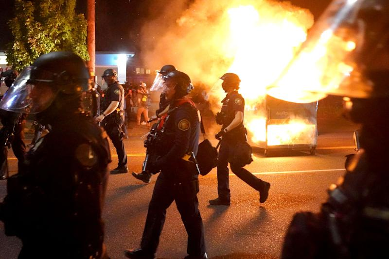 Portland police walk past a dumpster fire during a crowd dispersal on August 14, 2020 in Portland, Oregon. Source: Getty