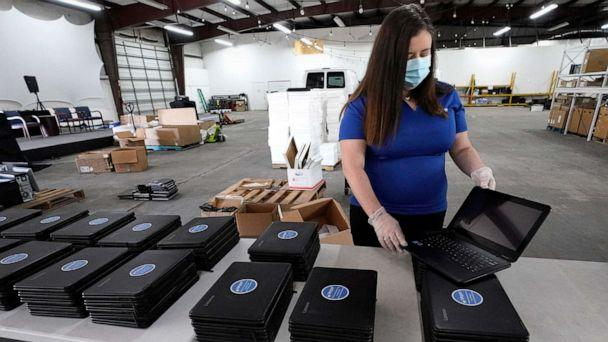 PHOTO: Chief Executive Officer Megan Steckly readies computers to be distributed at Comp-U-Dopt, April 14, 2020, in Houston (David J. Phillip/AP)
