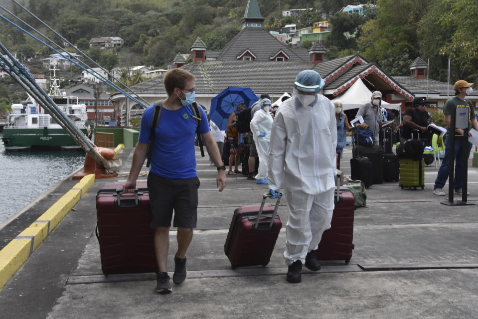 A healthcare worker helps an evacuee with his luggage as British, Canadian and U.S. nationals wait to board the Royal Caribbean cruise ship Reflection, in Kingstown, on the eastern Caribbean island of St. Vincent, Friday, April 16, 2021. La Soufriere volcano has shot out another explosive burst of gas and ash Friday morning as the cruise ship arrived to evacuate some of the foreigners who had been stuck on a St. Vincent island by a week of violent eruptions. (AP Photo/Orvil Samuel)