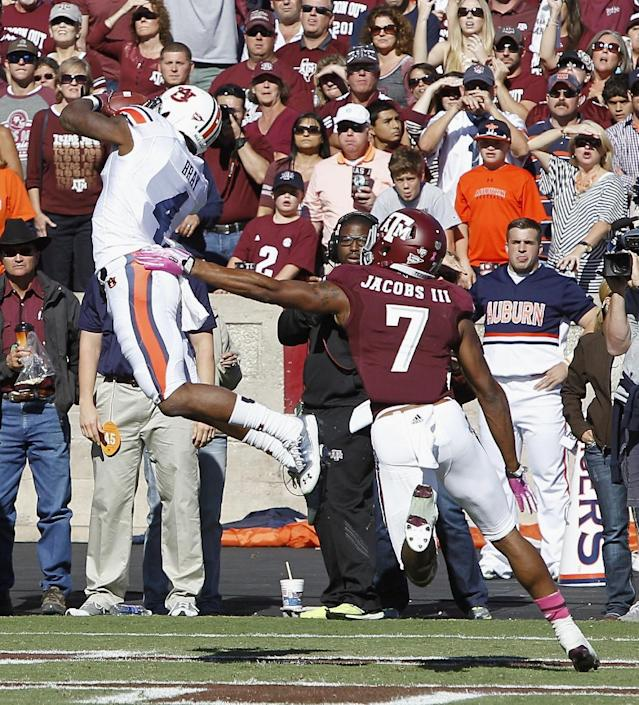 Auburn wide receiver Quan Bray (4) catches a pass for a touchdown in front of Texas A&M defensive back Tramain Jacobs (7) in the second quarter during an NCAA college football game Saturday, Oct. 19, 2013, in College Station, Texas. (AP Photo/Bob Levey)