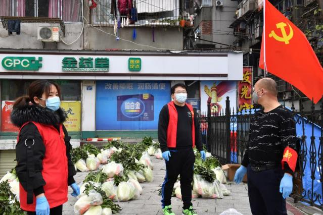 Volunteers wearing face masks stand next to vegetables to be delivered to residents of a residential area in Wuhan