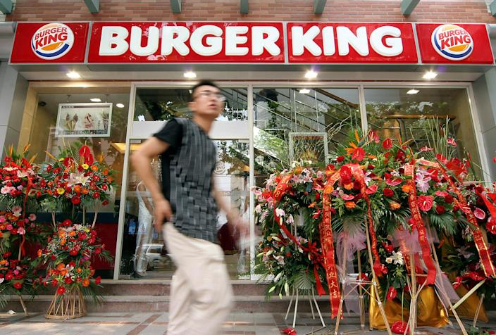 A Chinese man walks past in front of a Burger King restaurant as it opens its first restaurant in mainland China on Monday, June 27, 2005 in downtown Shanghai, China. The Burger King, operating more than 11,000 restaurants in 65 countries and territories worldwide, joined a competitive Chinese first food market. (AP Photo)