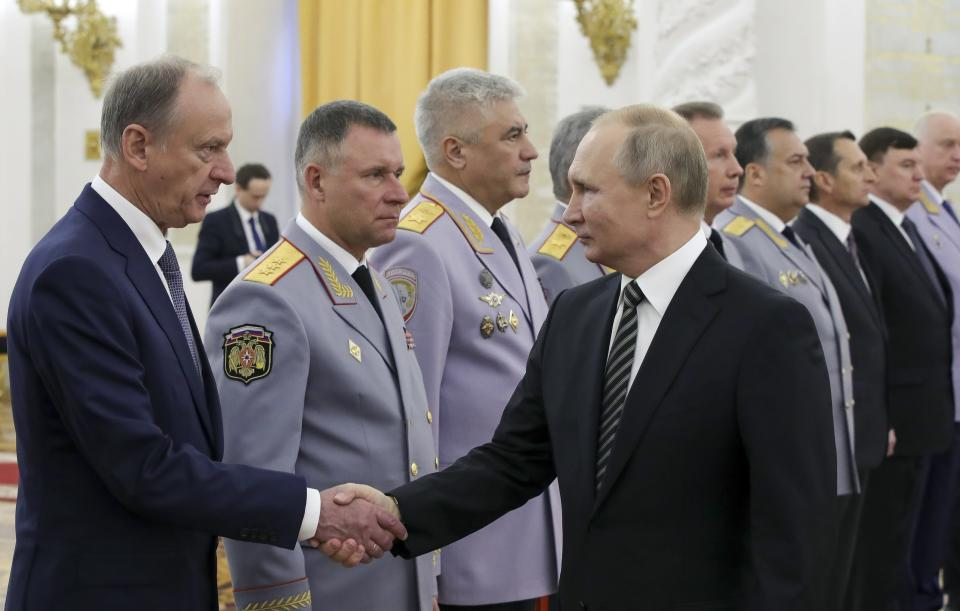 Russian President Vladimir Putin shakes hands with Russian Security Council chairman Nikolai Patrushev, left, as he greets senior military officers during a meeting in Moscow, Russia, Wednesday, Nov. 6, 2019. Putin said Russia's new weapons have no foreign equivalents but he insists the country will not use them to threaten anyone. (Mikhail Klimentyev, Sputnik, Kremlin Pool Photo via AP)