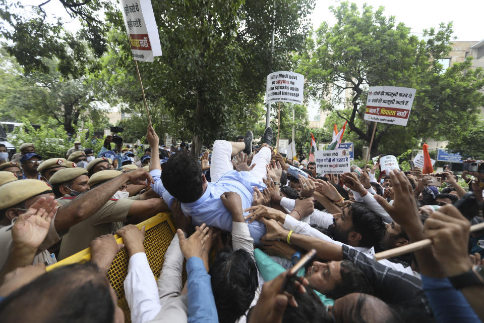Congress party workers help their leader cross over a police barricade during a protest accusing Prime Minister Narendra Modi's government of using military-grade spyware to monitor political opponents, journalists and activists in New Delhi, India, Tuesday, July 20, 2021. The protests came after an investigation by a global media consortium was published on Sunday. Based on leaked targeting data, the findings provided evidence that the spyware from Israel-based NSO Group, the world's most infamous hacker-for-hire company, was used to allegedly infiltrate devices belonging to a range of targets, including journalists, activists and political opponents in 50 countries. (AP Photo/Manish Swarup)