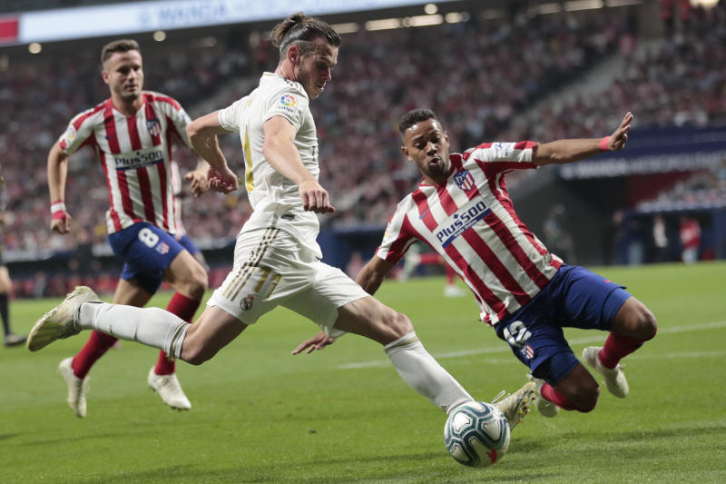 Atletico Madrid's Renan Lodi dives to block a pass by Real Madrid's Gareth Bale, center, during the Spanish La Liga soccer match between Atletico Madrid and Real Madrid at the Wanda Metropolitano stadium in Madrid, Saturday, Sept. 28, 2019. (AP Photo/Bernat Armangue)