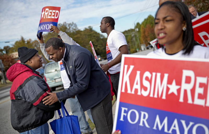 Lonnie Green, left, talks with Atlanta Mayor Kasim Reed as he campaigns at an intersection in west Atlanta, Tuesday, Nov. 5, 2013. Voters head to the polls Tuesday to decide whether Mayor Reed has earned a second term. Reed faces three challengers. (AP Photo/David Goldman)