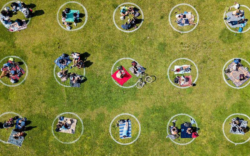 An aerial view shows people gathered inside painted circles on the grass encouraging social distancing at Dolores Park in San Francisco - JOSH EDELSON/AFP