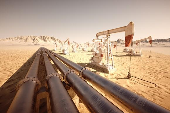 A series of pipes next to some oil pumps in a desert landscape