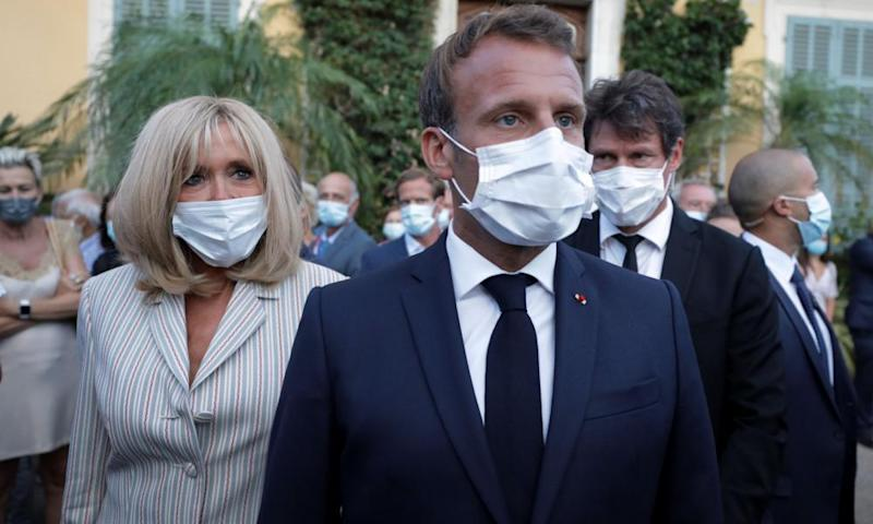 President Macron and wife Brigitte wearing masks at a public engagement. Mask-wearing has become a subject of controversy in Marseille.