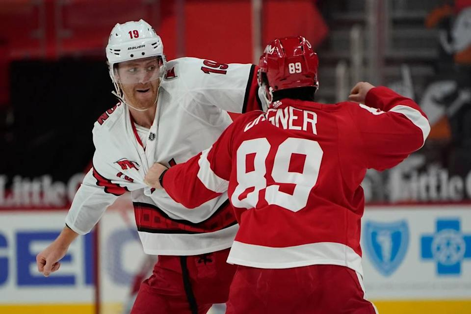 Carolina Hurricanes defenseman Dougie Hamilton (19) and Detroit Red Wings center Sam Gagner (89) fight in the second period of an NHL hockey game Thursday, Jan. 14, 2021, in Detroit. (AP Photo/Paul Sancya)