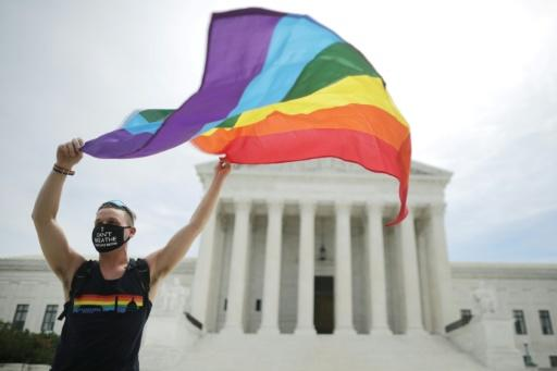Joseph Fons holds a Pride Flag in front of the US Supreme Court building after the court ruled that LGBT people cannot be disciplined or fired based on their sexual orientation