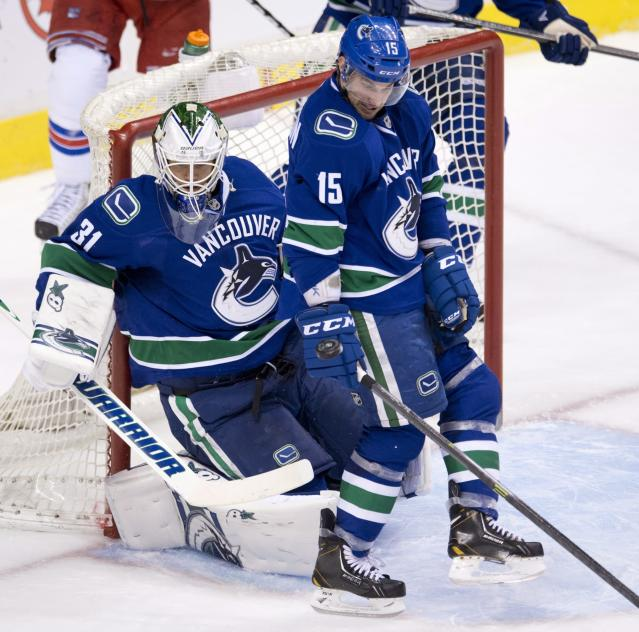 Vancouver Canucks goalie Eddie Lack (31) and Brad Richardson (15) stop a shot from the New York Rangers during the second period of NHL action in Vancouver, British Columbia, Tuesday, April 1, 2014. (AP Photo/The Canadian Press, Jonathan Hayward)