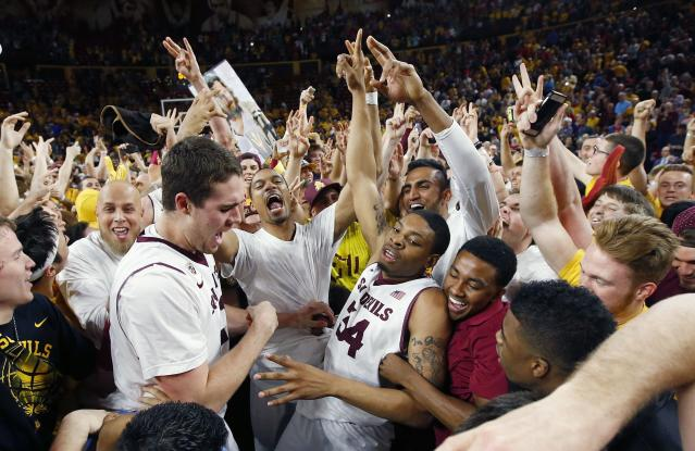 Arizona State's Jermaine Marshall (34) celebrates with teammates and fans after an NCAA college basketball game win against Arizona, Friday, Feb. 14, 2014, in Tempe, Ariz. Arizona State defeated Arizona 69-66 in double overtime. (AP Photo/Ross D. Franklin)