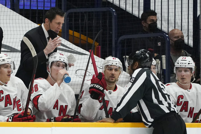 Carolina Hurricanes head coach Rod Brind'Amour, left, questions a call during the first period in Game 4 of an NHL hockey Stanley Cup first-round playoff series against the Nashville Predators Sunday, May 23, 2021, in Nashville, Tenn. (AP Photo/Mark Humphrey)