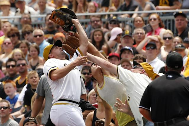 Pittsburgh Pirates first baseman Gaby Sanchez, left, makes the catch in a crowd of fans on a foul ball by Colorado Rockies' Drew Stubbs to end the first inning of a baseball game in Pittsburgh, Sunday, July 20, 2014. (AP Photo/Gene J. Puskar)