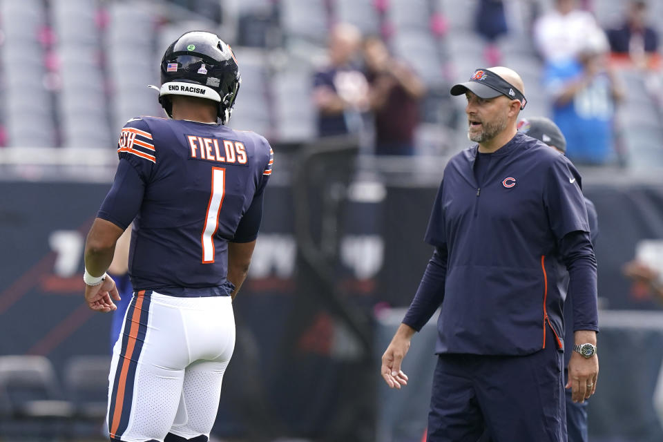 Chicago Bears quarterback Justin Fields listens to head coach Matt Nagy before an NFL football game against the Detroit Lions Sunday, Oct. 3, 2021, in Chicago. (AP Photo/Nam Y. Huh)