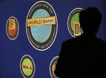 A man is silhouetted against the logo of the World Bank at the main venue for the IMF and World Bank annual meeting in Tokyo