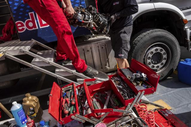 In this Saturday, Jan. 11, 2020 photo, Red Bull mechanics work at the Dakar Rally bivouac in Riyadh, Saudi Arabia. Formerly known as the Paris-Dakar Rally, the race was created by Thierry Sabine after he got lost in the Libyan desert in 1977. Until 2008, the rallies raced across Africa, but threats in Mauritania led organizers to cancel that year's event and move it to South America. It has now shifted to Saudi Arabia. The race started on Jan. 5 with 560 drivers and co-drivers, some on motorbikes, others in cars or in trucks. Only 41 are taking part in the Original category. (AP Photo/Bernat Armangue)