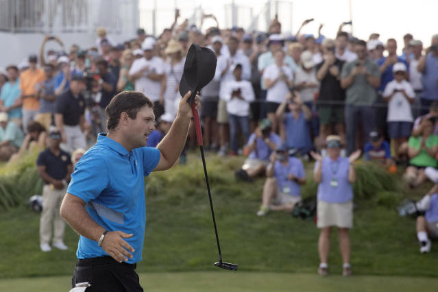 Patrick Reed tips his cap on the 18th hole as he wins on the Northern Trust golf tournament at Liberty National Golf Course, Sunday, Aug. 11, 2019, in Jersey City, N.J. (AP Photo/Mark Lennihan)