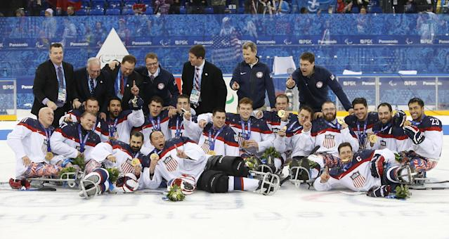 United States players and team officials pose for a team photo after they won gold medals at ice sledge hockey match between United States and Russia at the 2014 Winter Paralympics in Sochi, Russia, Saturday, March 15, 2014. United States won 1-0. (AP Photo/Pavel Golovkin)