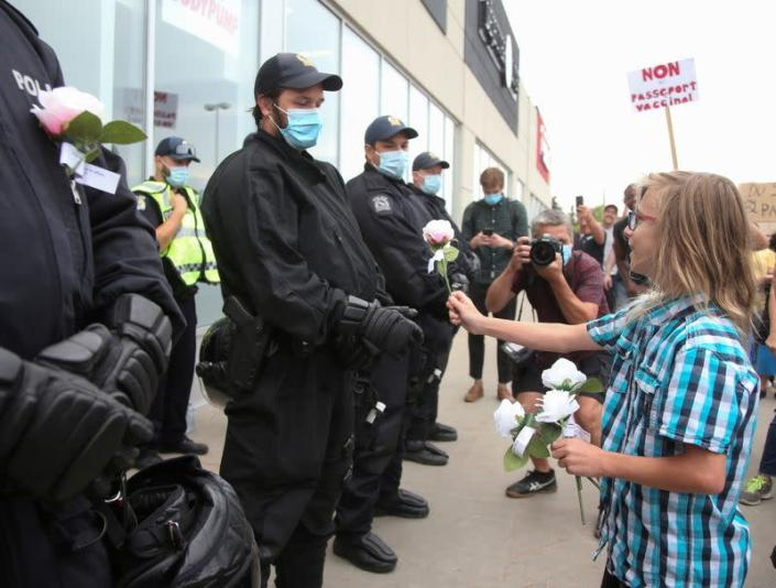 FILE PHOTO: Riot police stand in front of the entrance to an Econofitness gym as people gather to protest their use of a vaccine passport, in Laval, Quebec