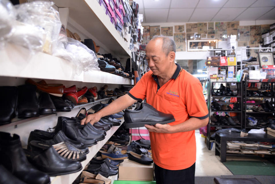 Wong arranges shoes for display at his shop. — Picture by Steven Ooi KE