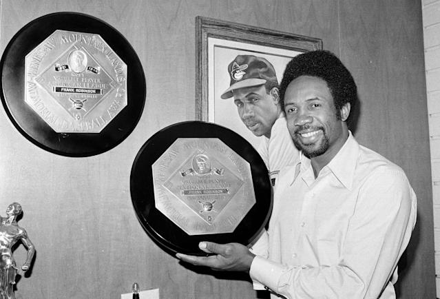 FILE - In this Dec. 3, 1971, file photo, Frank Robinson displays trophies he received for being the Most Valuable Player in both the American and National Leagues at his home in Los Angeles. Hall of Famer Frank Robinson, the first black manager in Major League Baseball and the only player to win the MVP award in both leagues, has died. He was 83. Robinson had been in hospice care at his home in Bel Air. MLB confirmed his death Thursday, Feb. 7, 2019. (AP Photo/Harold Filan, File)