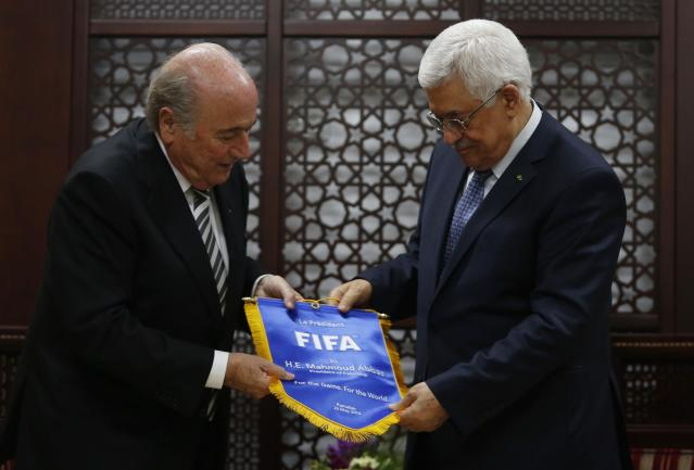 Palestinian president Mahmoud Abbas (R) receives a gift from FIFA President Sepp Blatter in the West Bank city of Ramallah May 26, 2014. REUTERS/Mohamad Torokman (WEST BANK - Tags: SPORT SOCCER POLITICS)