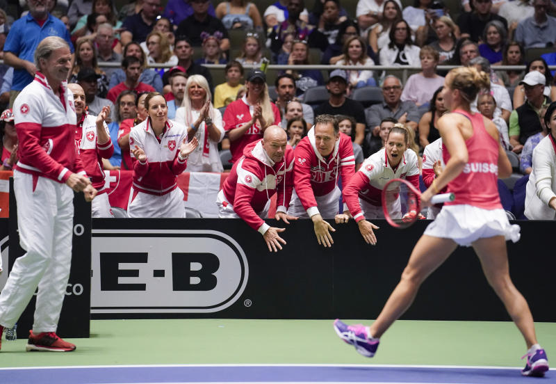 Members of the Swiss team congratulate Viktorija Golubic, right, after winning the first set against Madison Keys of the United States, during their playoff-round Fed Cup tennis match, Saturday, April 20, 2019, in San Antonio. (AP Photo/Darren Abate)