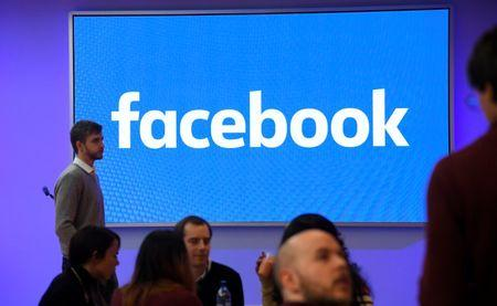 FILE PHOTO - People stand in front of a logo at Facebook's headquarters in London, Britain, December 4, 2017. REUTERS/Toby Melville