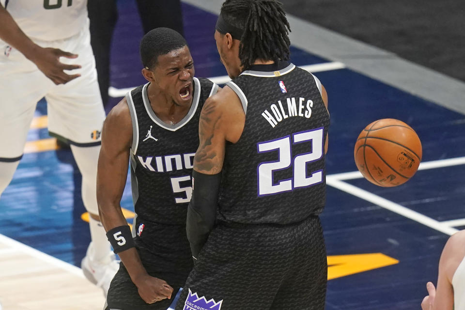 Sacramento Kings' De'Aaron Fox (5) celebrates with Richaun Holmes (22) after dunking against the Utah Jazz during the second half of an NBA basketball game Saturday, April 10, 2021, in in Salt Lake City. (AP Photo/Rick Bowmer)