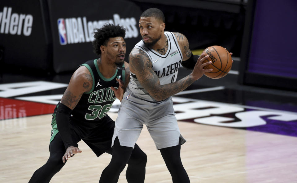 Portland Trail Blazers guard Damian Lillard, right, looks to drive the ball on Boston Celtics guard Marcus Smart, left, during the first half of an NBA basketball game in Portland, Ore., Tuesday, April 13, 2021. (AP Photo/Steve Dykes)