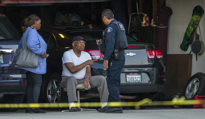 An Ontario Police officer interviews a neighbor sitting in his garage next door to a home where two children, an infant and a teenager, were found dead with their mother, who was unresponsive, Tuesday, Aug. 20, 2019, in Ontario, Calif. (Terry Pierson/The Orange County Register via AP)