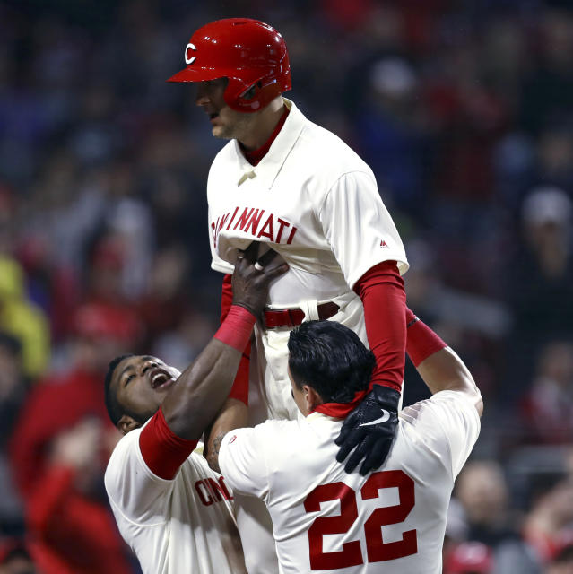 Cincinnati Reds' Nick Senzel is lifted by teammates Yasiel Puig, left, and Derek Dietrich, right, after hitting his first home in the majors, during the fifth inning of the team's baseball game against the San Francisco Giants, Saturday, May 4, 2019, in Cincinnati. (AP Photo/Aaron Doster)