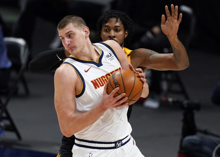 Denver Nuggets center Nikola Jokic, front, works the ball inside as Utah Jazz center Derrick Favors defends in the first half of an NBA basketball game Sunday, Jan. 31, 2021, in Denver. (AP Photo/David Zalubowski)