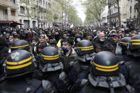 Riot police officers frame demonstrators during May Day march, Saturday, May 1, 2021 in Paris. Workers and union leaders dusted off bullhorns and flags that had stayed furled during coronavirus lockdowns for slimmed down but still boisterous May Day marches on Saturday, demanding more labor protections amid a pandemic that has turned economies and workplaces upside down. (AP Photo/Lewis Joly)